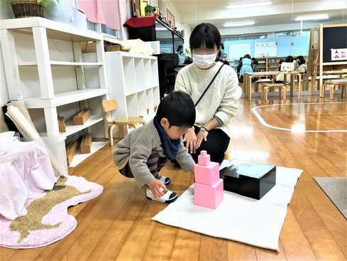 1歳児がモンテッソーリの個別活動で、ピンクタワーのお仕事に集中して活動しています。お母さまはお子様の様子を見守りながら観察しています。