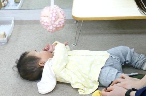 モンテッソーリ活動で、つるしてあるキッキングボールを見たり触ったりして、5ヵ月のお子様がタの死んでいます。