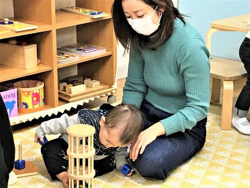 幼児教室のモンテッソーリの活動で、0歳児が玉の動きを集中して見ています。