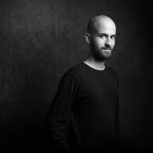 Sebstportrait des Fotografen Sebastian Kirsch vor einer dunklen Wand