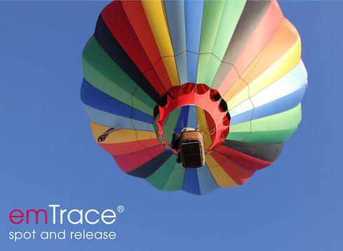 emTrace logo vor dem Hintergrund eines aufsteigenden Heißluftballons