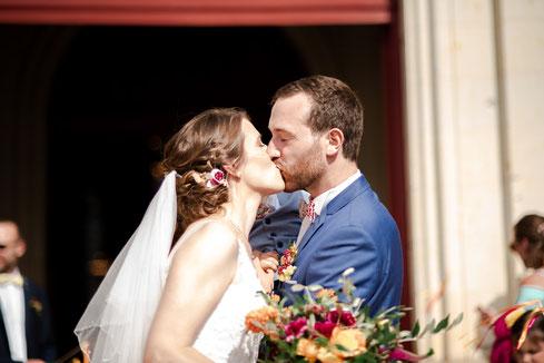 Baiser des mariées à la sortie d'église, organisation et décoration d'un mariage coloré par My Daydream Wedding, dans la région de Nantes