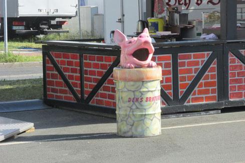 Dieses Foto zeigt einen Mülleimer vor einem Jahrmarkt in Form eines stilisierten Schweinskopfes.