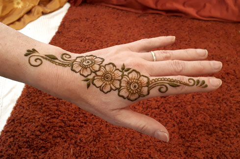Hand adorned with mehndi at a music festival