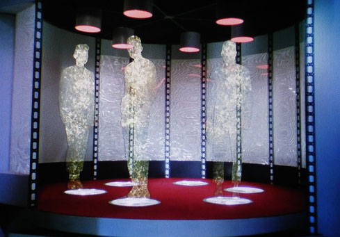 Image of Federation crew members materializing on the transporter pad in the original Star Trek series.