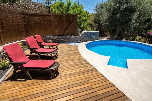 gemütlicher Pool mit Liegefläche aus Holz.