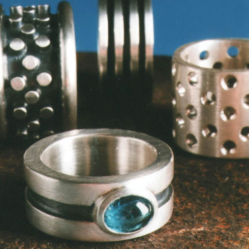 Massiven Silber Ringe mit geradlinigen Rillen und geschwärzten geometrischen Mustern.