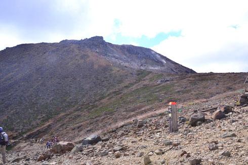 峯の茶屋から山頂を望む。                                                                手前の人が歩いている登山道が県営駐車場への道です。上の方に山腹を横切る道が見える。これがロープウェイ山頂駅への道です。
