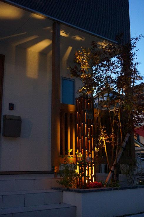 ランプカバー表札から伸びる光が植栽、そしてポーチの天井も照らす。