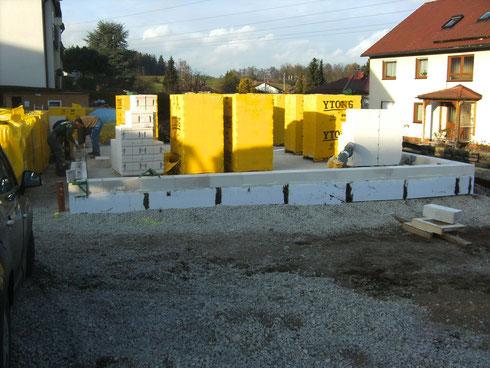 Die erste Steinreihe ist gesetzt. Die Seiten der Bodenplatte sind doppelt isoliert. Es ist Mitte November.