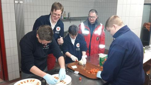 Einsatzkräfte beim Anrichten der Speisen in der Küche