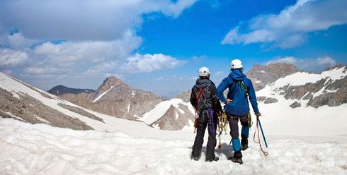zwei Bergsteiger die auf einem Gipfel die Aussicht genießen; Steigflug Unternehmensberatung