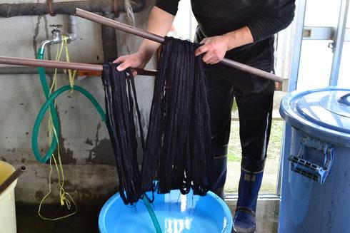 濃い色に仕上がった糸を水洗します