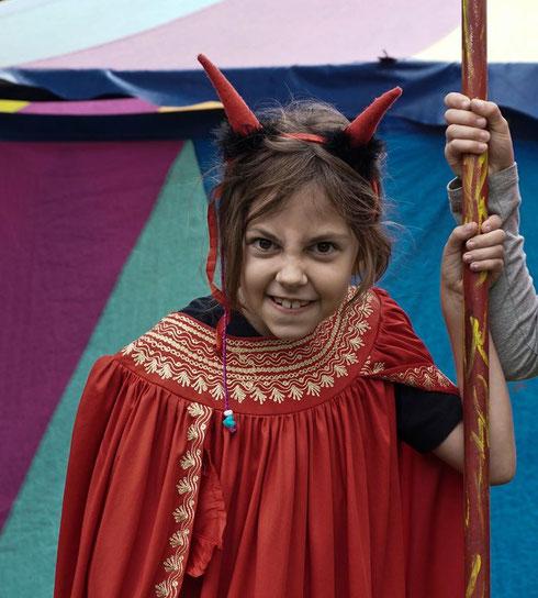 Ein Mädchen im Teufelskostüm macht eine (gespielt) böse Grimasse in die Kamera.