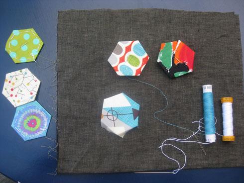 über papierschablonen gebügelte stoffsechsecke werden von hand zusammengenäht und auf die Unterlage appliziert