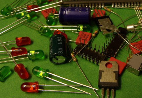 Verschiedene elektronische Bauteile wie LEDs, Kondensatoren, ICs und Widerstände