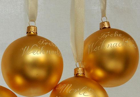 Goldene Weihnachtskugeln mit Kalligraphie
