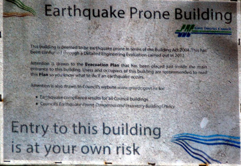 'Earthquake Prone Building' sign on wharfside building in Greymouth, Westland