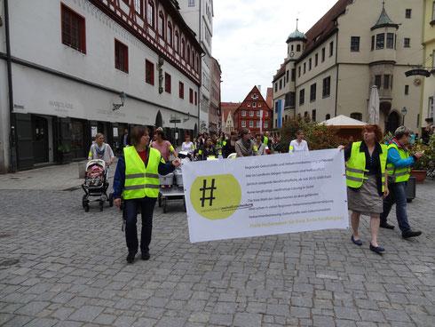 Gemeinsam ziehen Eltern und freiberufliche Hebammen durch die Fußgängerzone