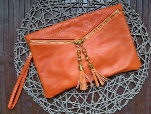 Elegante pochette en cuir orange et ses 2 bijoux assortis (vendu avec bandoulière pour une utilisation en sac). Dimension: 18 x 26 cm. Prix 20.00 € (frais de port Colissimo 6.60 €)