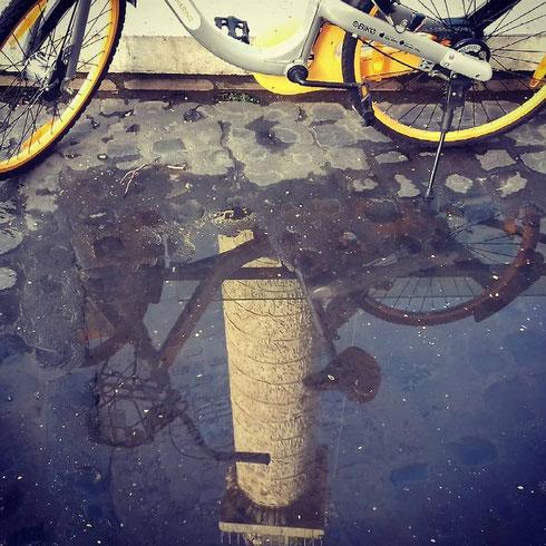Passato il temporale, la bici parcheggiata ai piedi della colonna Traiana aspetta solo qualcuno che voglia solcare le acque con lei