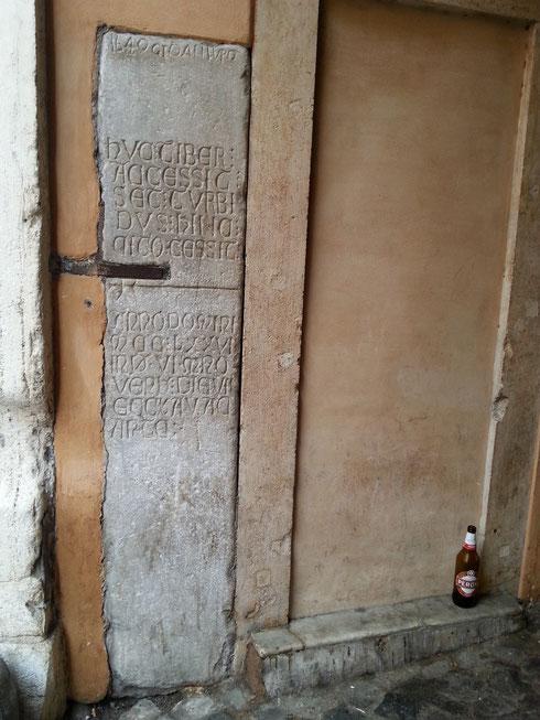La targa di via Arco dei Banchi è la più antica a ricordare un'inondazione del Tevere, datata 1277. La bottiglia di birra accanto sembra, invece, abbastanza recente...