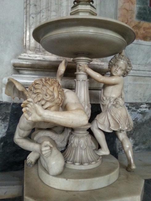 Datata 1860, l'acquasantiera realizzata da Pietro Galli per san Paolo fuori le mura mostra Satana sconfitto e un bambino che si protegge attingendo l'acqua benedetta.