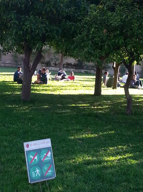 Giardino degli Aranci: in primo piano il cartello che vieta di calpestare il prato, in secondo piano déjeuner sur l'herbe. Delle due una: o si toglie il cartello o si chiede alle persone di alzarsi...