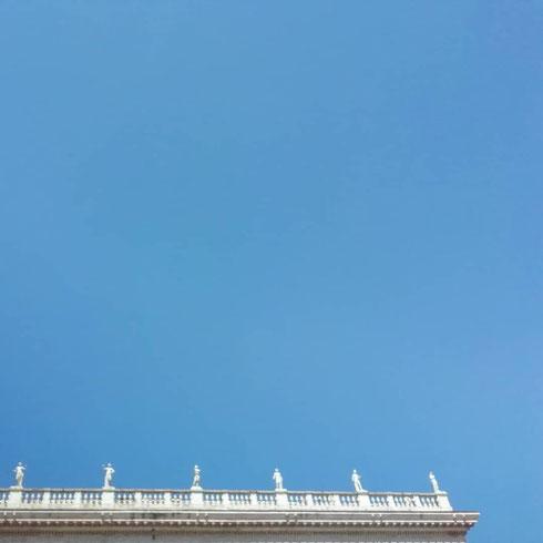 Nel cielo sopra al Campidoglio fanno capolino le statue di palazzo Nuovo