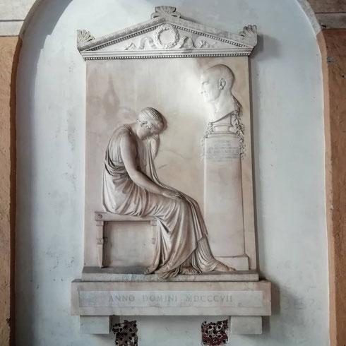Ancor prima di entrare, la basilica dei santi Apostoli svela i suoi capolavori: il portico conserva infatti, tra tanti frammenti architettonici, anche la stele che Antonio Canova realizzò in memoria dell'incisore Giovanni Volpato