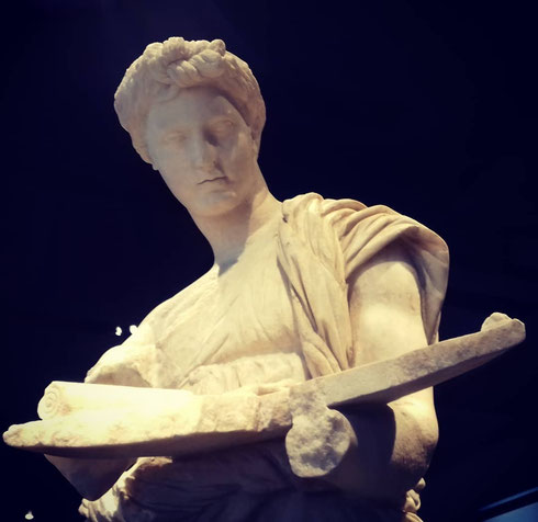 La fanciulla di Anzio rappresenta forse una sacerdotessa, tutta presa nel controllare gli strumenti necessari al rito