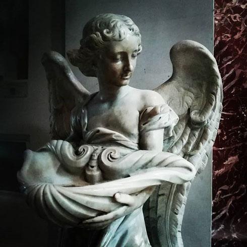 Un angelo gentile porge l'acqua ai fedeli all'ingresso della basilica di santa Maria degli Angeli