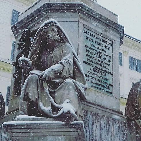 Sembra stupito, forse addirittura infastidito il profeta Isaia, mentre osserva la neve cadere seduto alla base della colonna dell'Immacolata