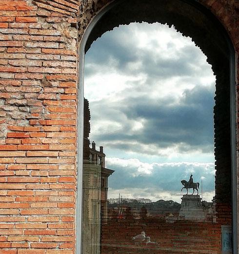 Vittorio Emanuele II (si) riflette nel finestrone del museo dei fori imperiali, ospitato nelle sale dei mercati di Traiano