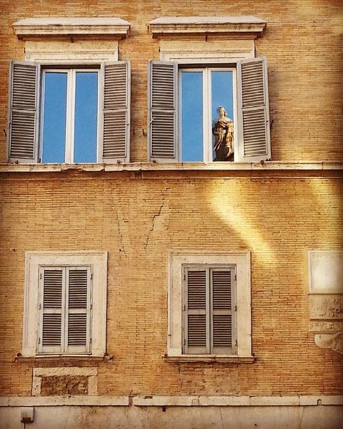 Scherzi del caldo, semplice riflesso o la statua del banco di Santo Spirito a largo Tassoni è davvero affacciata dalla finestra di fronte?