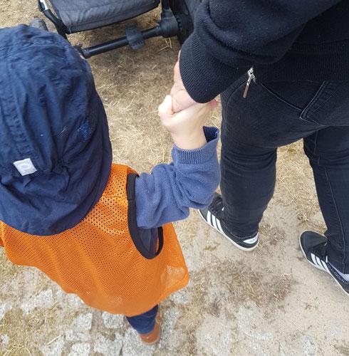 Kleinkind Hand in Hand mit Kita-Erzieherin während der Eingewöhnung.