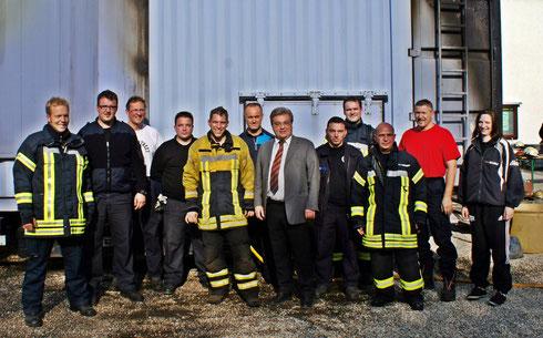 Teilnehmer des letzten Durchgangs fassen Ausbilder Thomas Schumm (gelbe Jacke) und Verbandsbürgermeister Uwe Schwind (HuPF Anzug) vor dem Brandübungscontainer zum Gruppenbild zusammen.