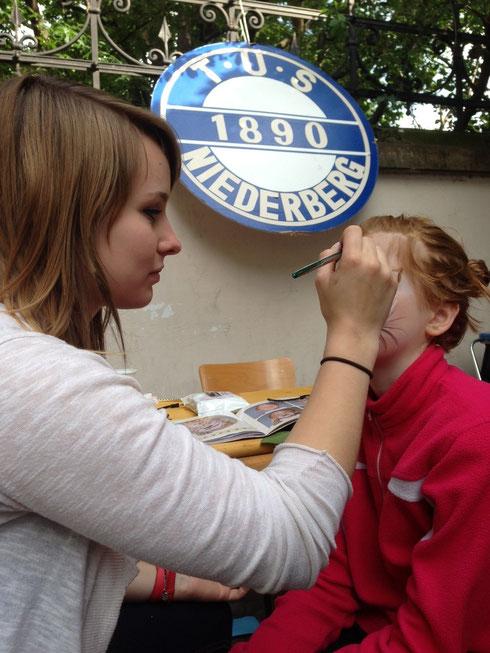 Übungsleiterin Marie-Lena Frensch schminkt eines von vielen 100 Kindern