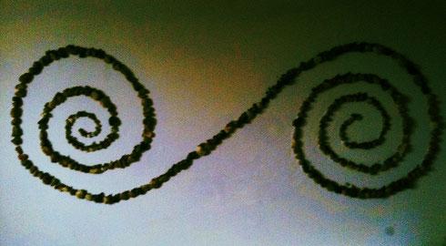 Die Spirale, ein altes keltisches Symbol in Form der Ewigkeit aus größeren Kieselsteinen