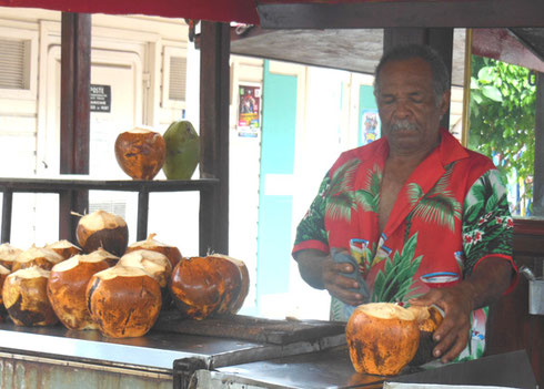 A vendor sells coconut milk at a stall in Marigot on the French side of St. Martin