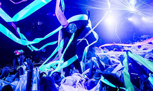 Blue man with blue face make-up with lots of streamers