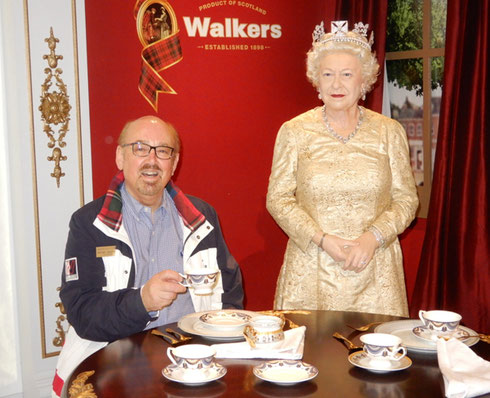 A photo of Randall standing next to Queen Elizabeth photo at Madame Tussaud's
