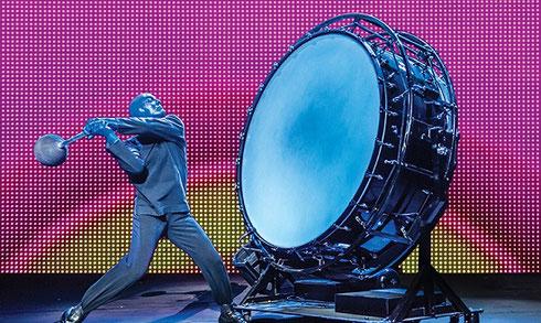 A man in blue makeup strikes a huge drum