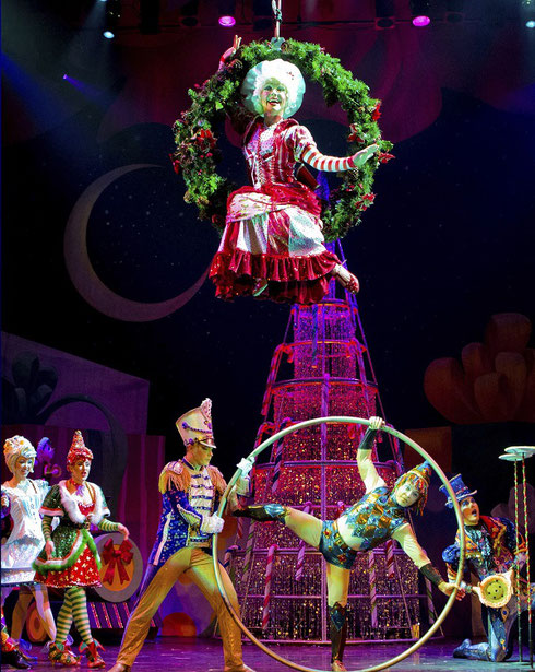 Mother Christmas descends to the stage on a huge wreath