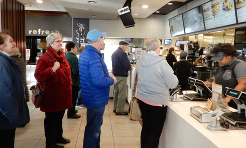 A group of Travelers standing in line for breakfast at McDonald's