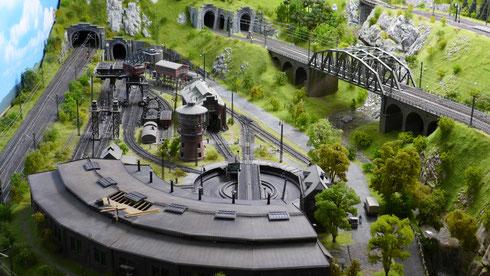 """Links das Bahnbetriebswerk (Lokschuppen mit kleinem """"Dachschaden"""") und rechts die Paradestrecke in vorbildlicher Landschaft."""