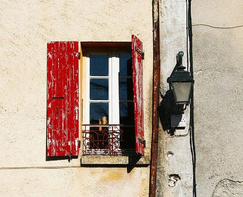 des volets rouges à moitié ouverts, de l'autre côté de la vitre, on devine un interieur
