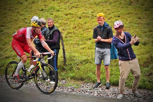 Tour de France 2014. Ein Zuschauer macht am Straßenrand mit dem Rücken zum Rennfahrer Adrien Petit ein Selfie. Sein neben ihm stehender Freund schaut ängstlich zu. Foto: Tobias Bunners