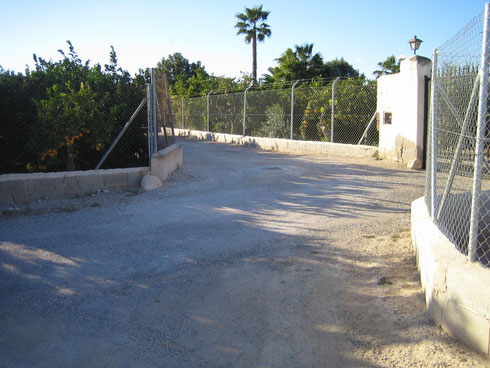 Links geht es zur Straße, rechts das Tor des Nachbarn, mittig die Einfahrt zum Refugio