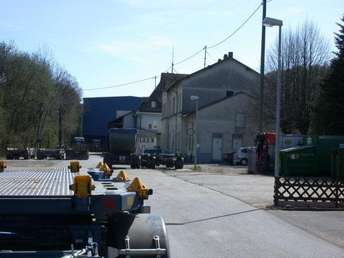 2011: Vorplatz und Empfangsgebäude des Bahnhofs Neunkirchen (Kreis Siegen), zahlreiche Lastwagen und Schrott-Container veranlassen die Reisenden zum Hindernislauf